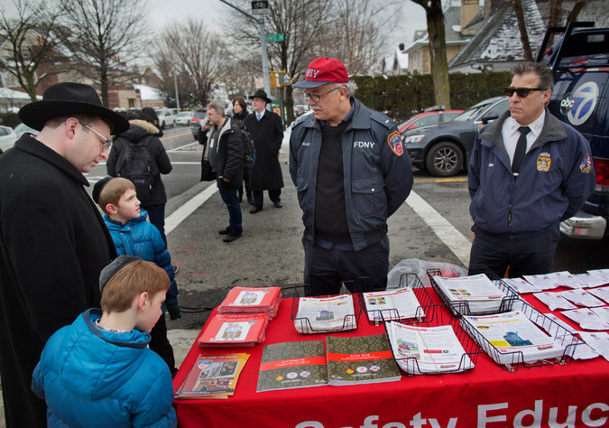 Fire officials set up an information table in Brooklyn to teach residents about fire safety. (Photo courtesy of the New York Times.)